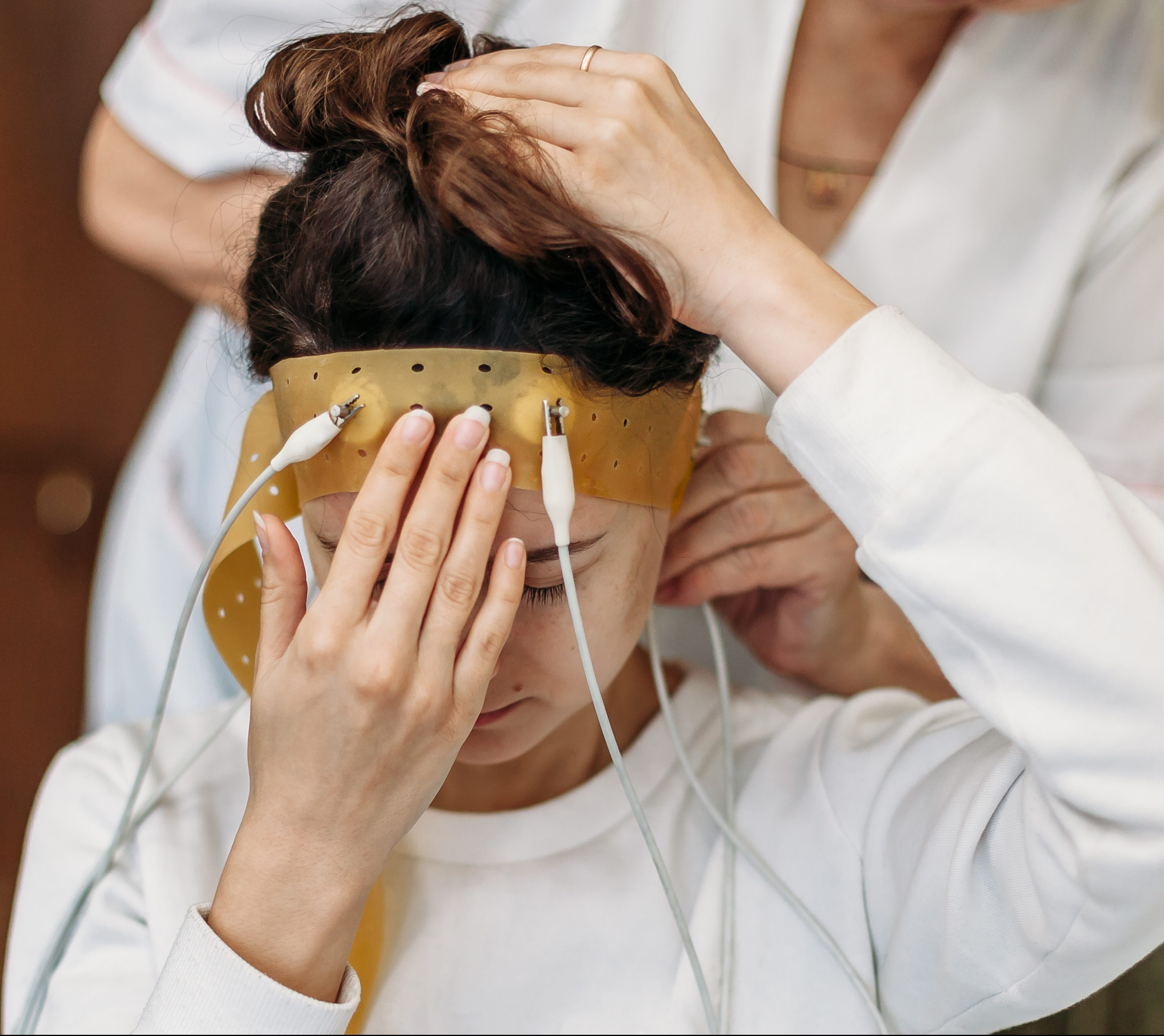 A young woman is sitting in a chair as a doctor dawns a silicone headband containing electrodes on her head.